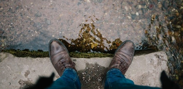 A man protecting his leather shoes from the puddle of rainwater in Washington