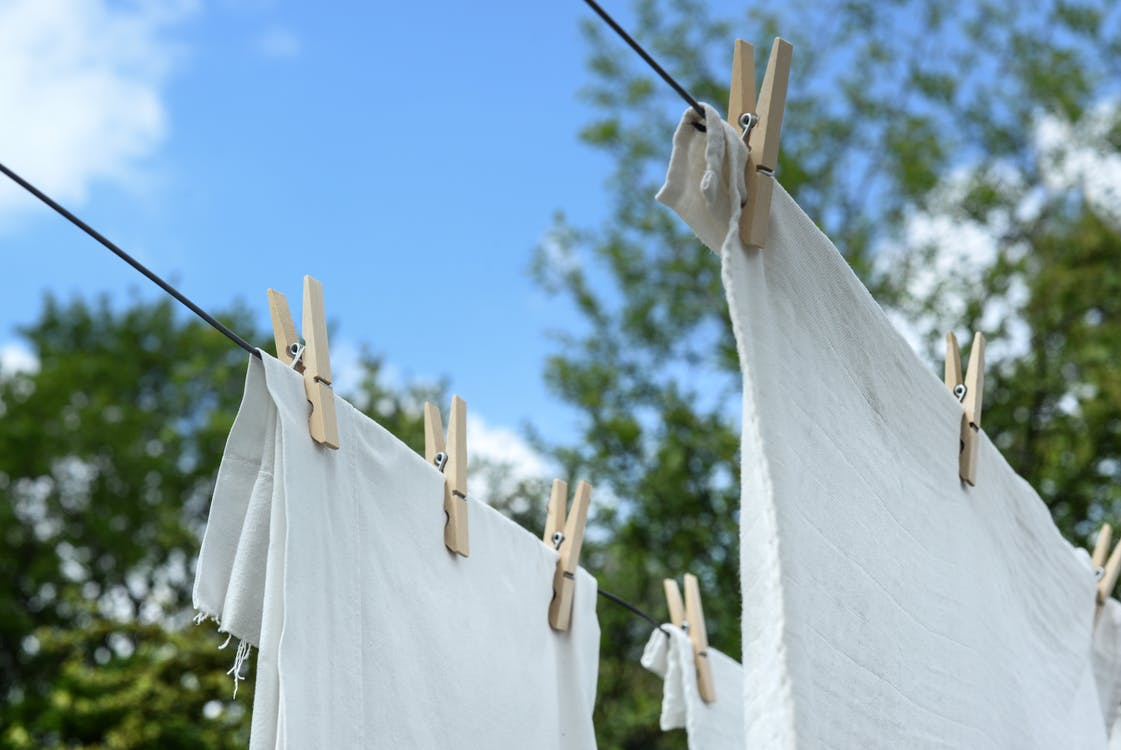 White sheets drying outside on pegs and a laundry wire