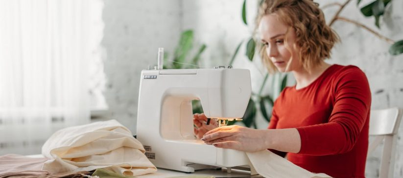A woman in a red dress sitting on a chair and tailoring her clothes on a sewing machine
