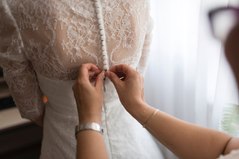 A woman closing the buttons on a wedding dress