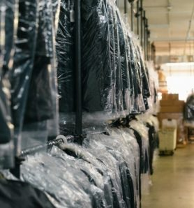 Wrapped in plastic sheets after being cleaned, black blazers are lined up on hangers to ensure they remain intact.