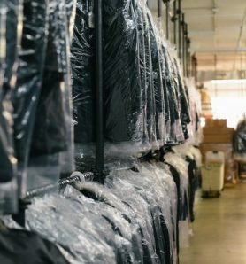 Racks of suits hanging in plastic sheets at a dry cleaning shop.